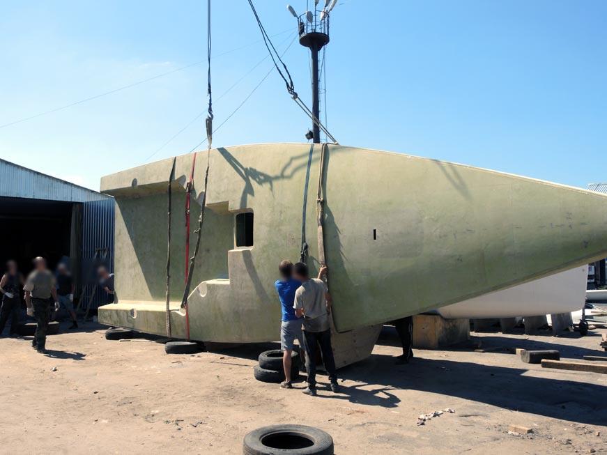 переворот корпуса пластиковой гоночной яхты на верфи